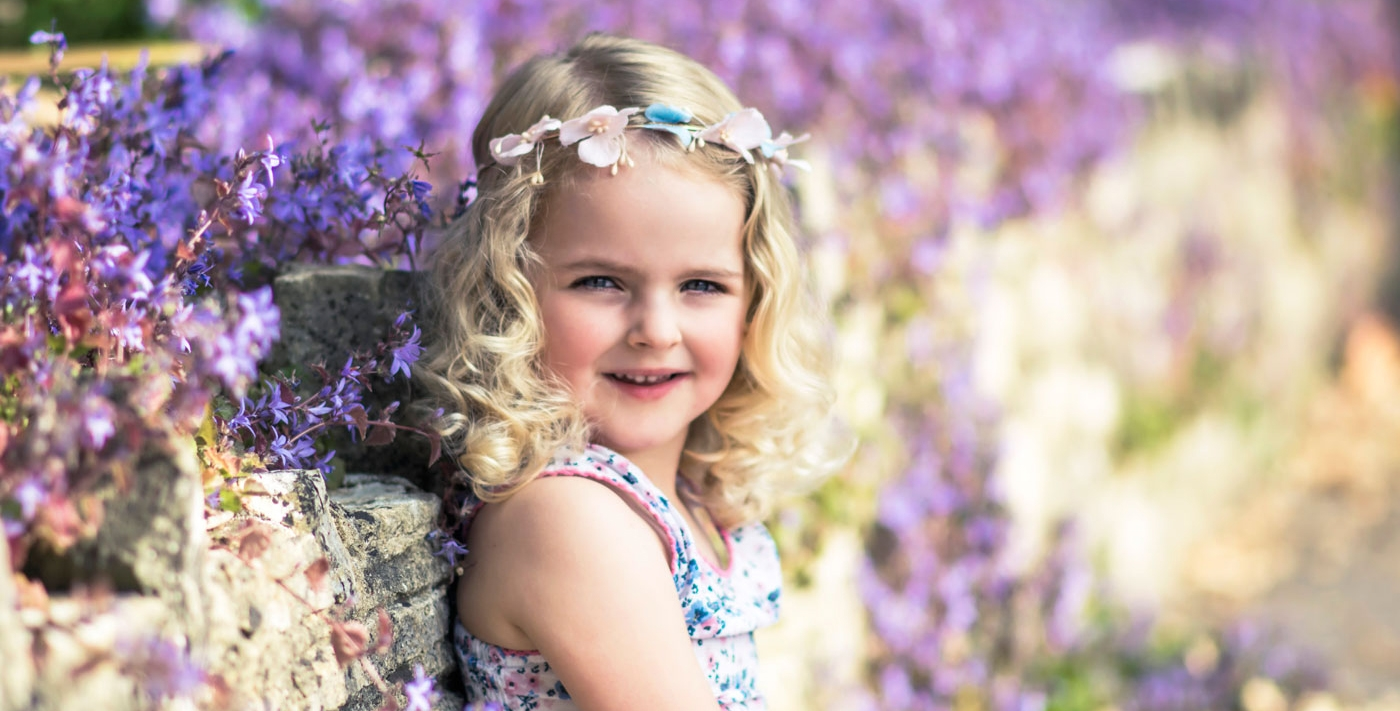 Girl in purple flower field by family photographer in Poole Iryna Photography